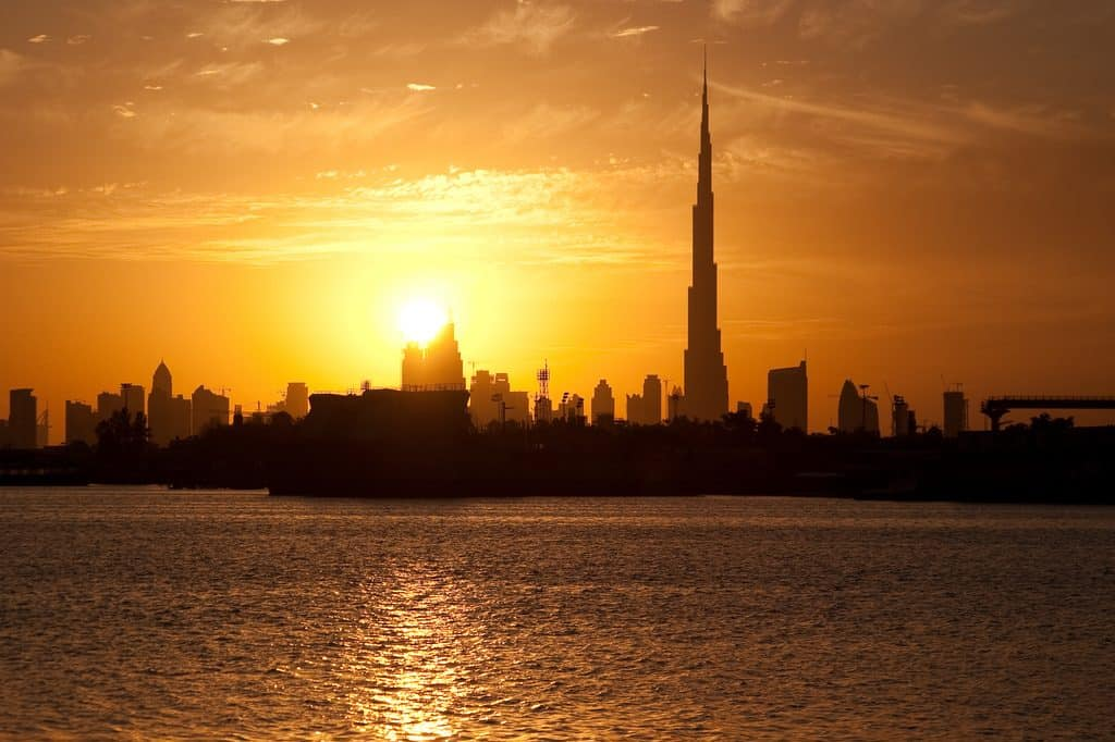 picture of dubai summer skyline with sun and water