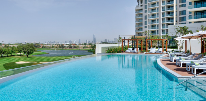 Swimming pool and sun loungers and amazing golf course view at Vida Hotel Emirates Hills in Dubai